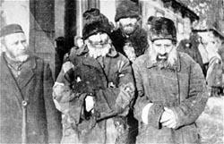 Vier Männer mit zerschlissenen Mänteln. Quelle: United States Holocaust Memorial Museum, Photograph #03846.