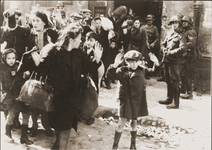 Szene aus dem Warschauer Ghetto. Der Junge im Vordergrund wurde später identifiziert als Tsvi C. Nussbaum. Quelle: Wikipedia.